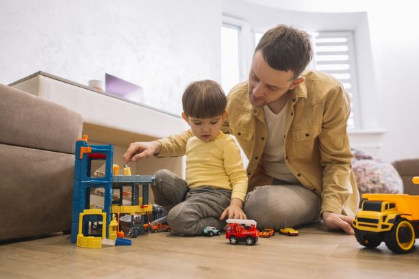 father-son-playing-with-trucks-lego-pieces